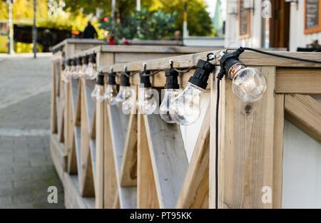 Eine Linie von kabelgebundenen Glühbirne edison Lampen mit LED-Glühlampen auf einer hölzernen Geländer außerhalb einer Coffee Shop in Norwegen. - Stockfoto