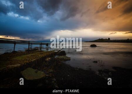 Sonnenuntergang von den Trondheimsfjorden, Strand in Vaeresholmen, Vaere. Lange Belichtung auf fließende Wolken und welligen Wasser. - Stockfoto