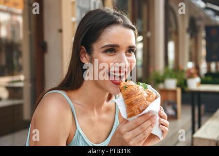Bild der junge lächelnde Frau sitzt im Cafe im Freien während des Essens Croissant. - Stockfoto