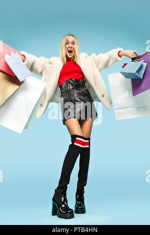In voller Länge Porträt einer wunderschönen Lächeln lustige blonde Frau zu Fuß mit bunten Einkaufstaschen über Blau studio Hintergrund isoliert. Die Lifestyle, Mode, Verkauf, shopaholic Konzept - Stockfoto