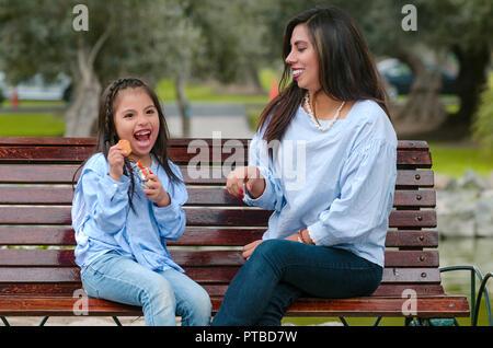 Mutter und ihre kleine Tochter auf einer Bank sitzen Essen ein Cookie im Park - Stockfoto