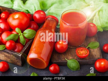 Flasche frische organische Tomatensaft mit frischen, rohen Tomaten in Kiste auf Küche Hintergrund. - Stockfoto