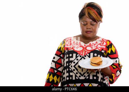 Studio Aufnahme von fetten schwarzen afrikanischen Frau Holding und Suchen auf bu - Stockfoto