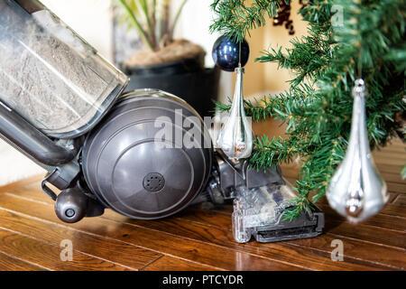 Nahaufnahme des aufrechten Staubsauger reinigen, saugen unter Weihnachten Baum Nadeln mit neuen Jahren Ornamente auf Hartholz Holzboden - Stockfoto