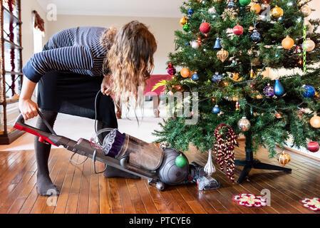 Junge Frau mit Staubsauger reinigen, saugen unter Weihnachten Baum Nadeln mit neuen Jahren Ornamente auf Hartholz Holzboden - Stockfoto