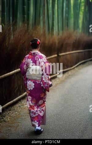 Japanische Frau in einem lila Kimono entlang Arashiyama Bambuswald, Kyoto, Japan - Stockfoto