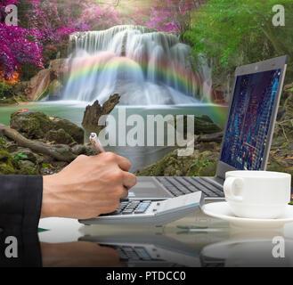 Unternehmer arbeiten mit dem Laptop auf dem wunderschönen Wasserfall in den tiefen Wald mit Regenbogen, Business Financial Concept - Stockfoto