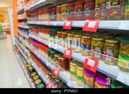 Verschwommenes Bild von Regalen mit Konserven im Supermarkt. - Stockfoto