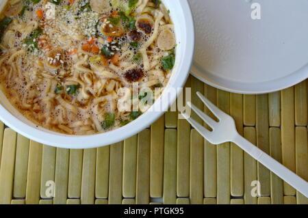 Instant Nudeln weich gekochte in Plastikbecher auf Bambus Platte - Stockfoto