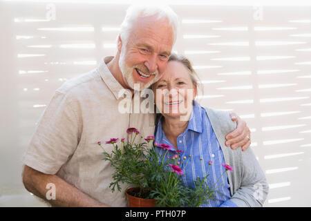 Portrait happy Active Senior Paar mit Blumentöpfen - Stockfoto