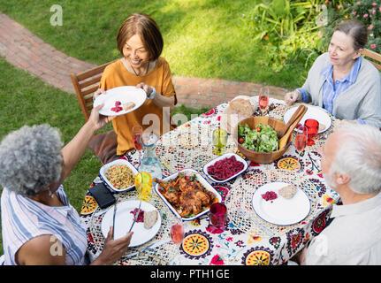 Ältere Freunde genießen Mittagessen in Terrasse Tisch - Stockfoto