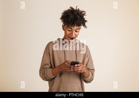Porträt von einem aufgeregten Jungen afro-amerikanische Mann im T-Shirt gekleidet, isoliert, holding Handy - Stockfoto
