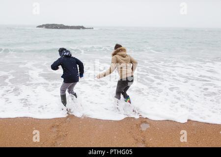 Verspielter Teenager Bruder und Tochter spielen im Winter Ocean Surf - Stockfoto