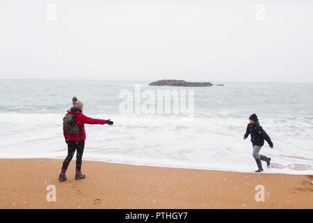 Verspielte Mutter und Sohn auf verschneiten Winter Ocean Beach - Stockfoto
