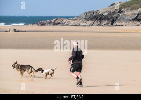 Ein Mann läuft mit seinen Hunden auf Crantock Beach in Newquay in Cornwall. - Stockfoto