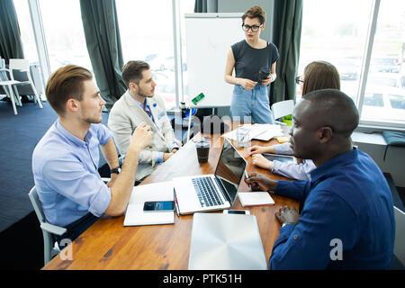 Diskussionen über neue Geschäftsideen. Fröhliche junge Frau, die in der Nähe von Whiteboard und lächelnd, während ihre Kollegen am Schreibtisch sitzen. - Stockfoto