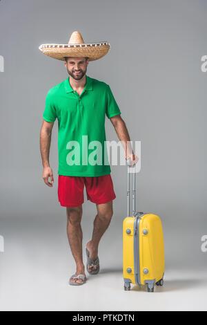 Lächelnd Traveler in der mexikanischen sombrero stehend mit Koffer auf Grau - Stockfoto