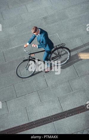 Hohe Betrachtungswinkel der Geschäftsmann in formalen Verschleiß Reiten Fahrrad- und Kontrolle Armbanduhr - Stockfoto