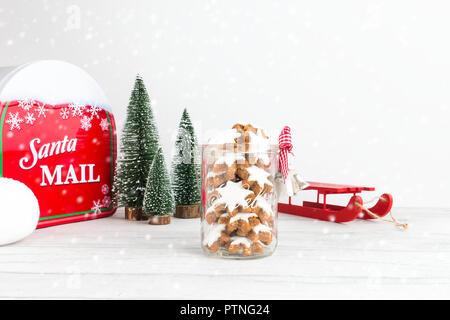 Weihnachtsplätzchen, Deutschen, Zimtsterne Zimtsterne in einem Glas mit Weihnachtsdekoration, einen Schlitten, Tannen, ein Santa Mailbox, eine Schneeballschlacht und ein - Stockfoto