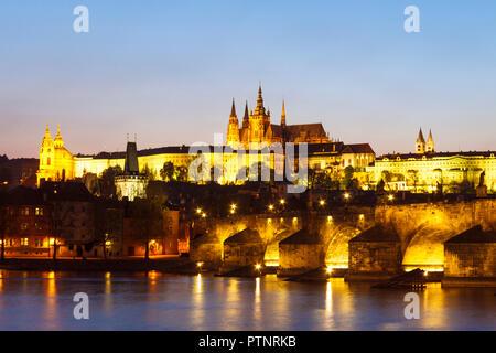 Prag, Tschechische Republik: Karlsbrücke, Veitsdom und Prager Burgkomplex leuchtet in der Dämmerung. - Stockfoto