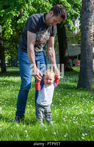 Alleinerziehende und 12 Monate alten Babys genießen im Freien - Happy Baby seine ersten Schritte auf grünem Gras - Stockfoto