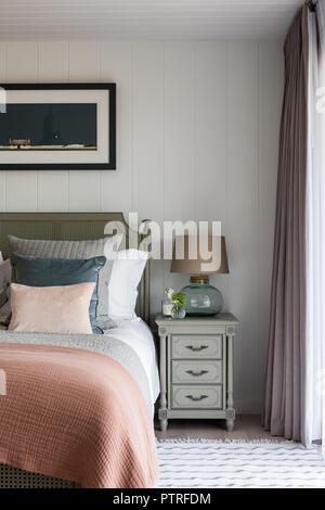 Pfirsich quilt auf Doppelbett mit gold Lampe auf dem Nachttisch - Stockfoto