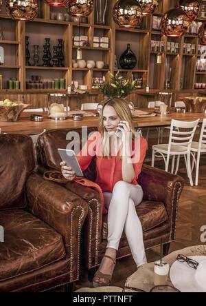 Frau im Kaffeehaus Mit Smartphone Und Tablet-PC (Model-Release) - Stockfoto