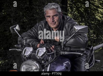 Aelterer Mann Sitzt in Lederjacke Auf Motorrad (Model-Release) - Stockfoto