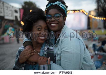 Porträt Lächeln, liebevolle Schwestern umarmen bei Movie im Park - Stockfoto