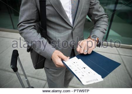 Geschäftsmann mit Flugticket der Zeit auf die Überprüfung der Armbanduhr - Stockfoto