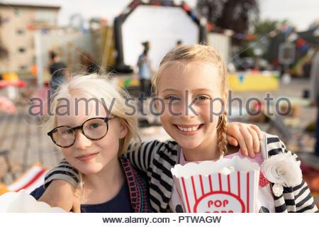 Porträt Lächeln, zuversichtlich, Schwestern mit Popcorn im Kino im Park - Stockfoto