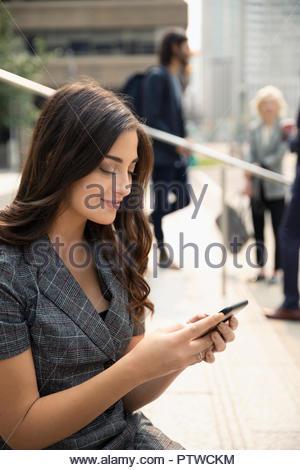 Lächelnden jungen Geschäftsfrau mit Smart Phone auf Schritte - Stockfoto
