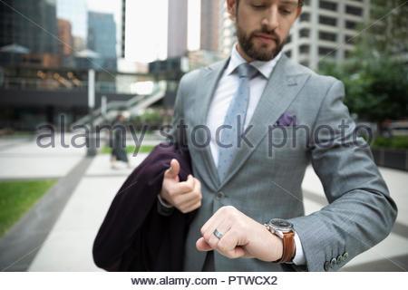 Unternehmer die Zeit, die auf die Überprüfung der Armbanduhr auf städtischen Bürgersteig - Stockfoto