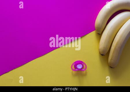 Baby pürieren in Löffel mit Nippel und Früchte auf lila Hintergrund - Stockfoto