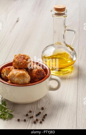 Gebratenes Fleisch Schnitzel aus weisser Keramik Soup Bowl, Glasflasche mit Sonnenblumenöl, Zweig der frische Petersilie und Pfeffer schwarz auf grau Holzbretter - Stockfoto