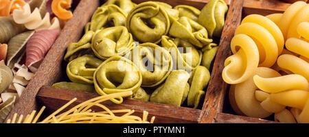 Hausgemachte Tortellini mit Spinat, Käse und Ricotta und sortierte Bunte italienische Pasta in Holzkiste. Gesundes essen Hintergrund Konzept. Banner. - Stockfoto