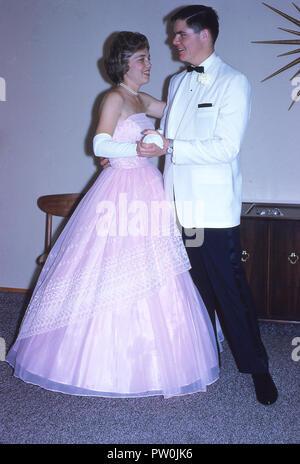 1962, Amerika, gehen zum Abschlußball ..... ein junger Mann mit einem weißen Smoking und und eine junge Frau eine lange Rüschen rosa Kleid stehen zusammen tragen für ein Bild, bevor Sie das Prom teilnehmen, ein traditioneller und wichtiger Ende der Amtszeit Tanz und gesellschaftliches Ereignis für uns Schülerinnen und Schüler. In den 50s und 60s, das Prom war mehr der Veranstaltung ein Paar, wo ein Junge ein Mädchen sein Date zu sein Bitten und würde Ihr Escort nach ihrer Abholung an ihrem Haus und viele Bilder gemacht! - Stockfoto