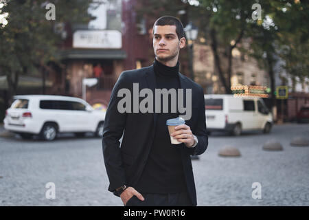 Selbstbewussten jungen Mann mit Kaffee, am frühen Morgen, zu Fuß in die Stadt - Stockfoto