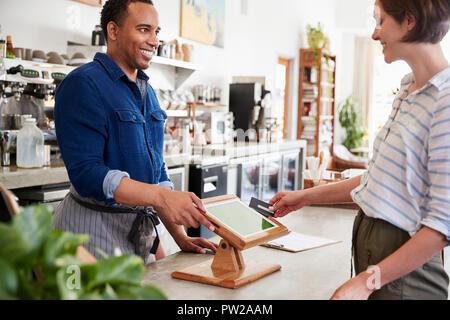 Weibliche Kunden kontaktlose Karte Zahlung im Cafe - Stockfoto