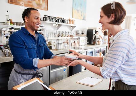 Männliche barista an eine weibliche Coffee shop kunde - Stockfoto