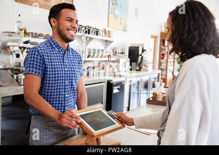 Männliche barista lächelt einen weiblichen Kunden in einem Coffee Shop - Stockfoto