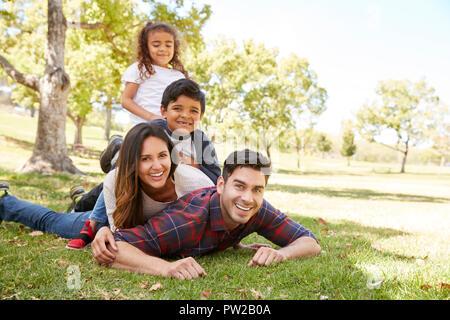 Junge Kinder und Eltern im Flor, die auf dem Gras, Porträt - Stockfoto