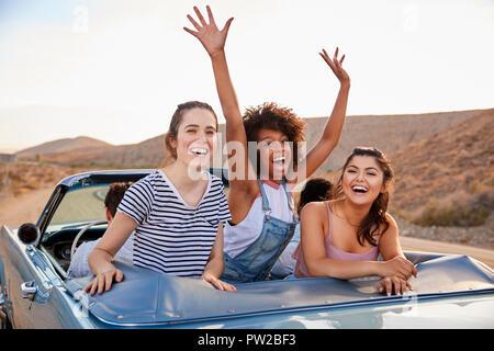 Portrait von drei weiblichen Freunde genießen Reise in oben offenen Classic Car - Stockfoto