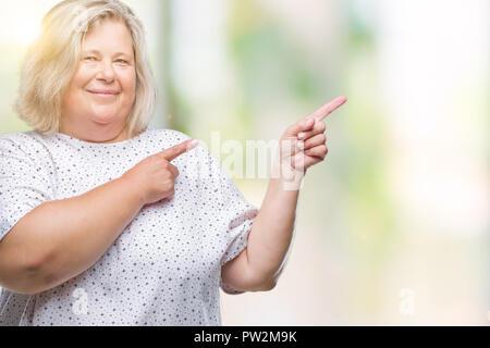 Senior Plus size kaukasische Frau über isolierte Hintergrund lächelt und schaut in die Kamera zeigte mit zwei Hände und Finger zur Seite. - Stockfoto