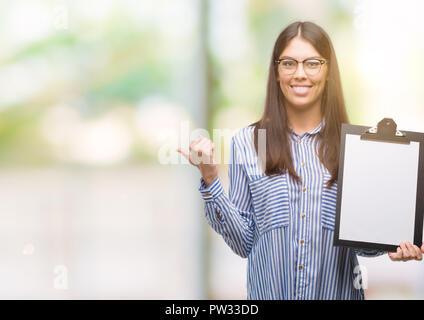 Junge Hispanic woman holding Zwischenablage zeigen und zeigt mit dem Daumen bis zu der Seite mit glücklichen Gesicht lächelnd - Stockfoto