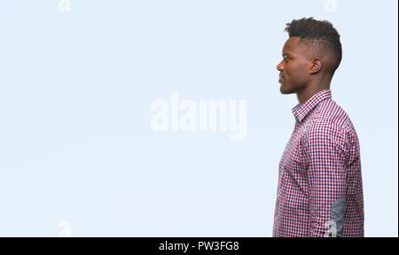 Junge afrikanische amerikanische Mann über isolierte Hintergrund auf der Suche nach Side, entspannen Profil mit natürliches Gesicht mit selbstbewussten Lächeln darstellen. - Stockfoto