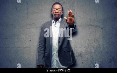 Afrikanischen schwarzen Mann mit Jacke mit schlechten Haltung, STOP-Schild mit Hand genervt, nein zu sagen, und die Sicherheit, die Verteidigung oder Beschränkung, vielleicht p - Stockfoto