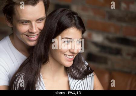 Attraktive junge Paar Lächeln und Umarmungen im Innenbereich - Stockfoto