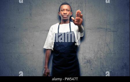 Afrikanischer Mann shop besitzer tragen Schürze mit schlechten Haltung, STOP-Schild mit Hand genervt, nein zu sagen, und die Sicherheit, die Verteidigung oder Beschränkung, Mai - Stockfoto