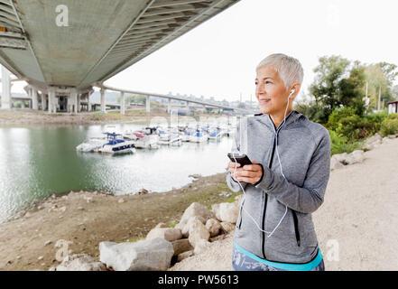Portrait von Aktive ältere, Frau Musik hören mit Smartphone, Training im Freien. - Stockfoto